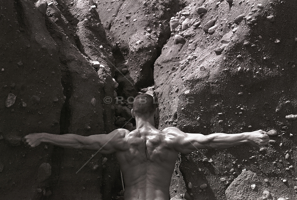fine art nude photograph of a man's back against a rock formation in Montauk, NY