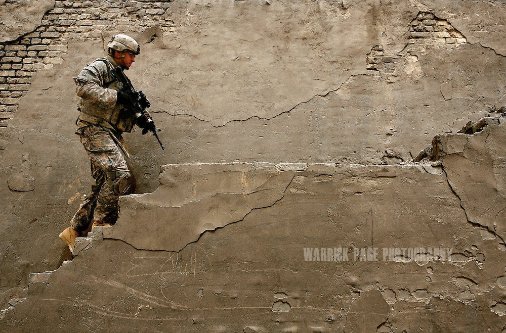 IRAQ, NARWAN - JULY 1: A US soldier with 2nd Brigade, 1st Armored Division, walks up stairs leading to the roof of a brick kiln at the Narwan brick factory, July 1, 2008 in Narwan, Iraq. Twenty miles east of Baghdad, the 170+ small brick factories employ about 30,000 Iraqis, shaping mud into bricks and fire them in kilns burning heavy fuel oil that produces acrid, black smoke visible from satellite imagery 50 miles above the earth's surface. The brick factory employs seasonal workers, many of whom are children - some are as young as four - in highly toxic conditions offering minimal food and water. Respiratory problems are common amongst the workers and children, with no medical personal available to treat them. (Photo by Warrick Page)