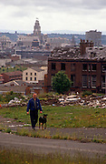 A wide landscape of dereliction and poverty during the early 1990s in the city of Liverpool, England. The Liver building is seen in the far distance as a symbol of the city centre beyond an empty street up which a solitary man walks his dog. Empty buildings await destruction after the terraced housing has long been razed to the ground in the 1960s - the impoverished population having moved out for a better life elsewhere.