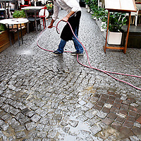A restuarant employee sprays the street down in Istanbul, Turkey