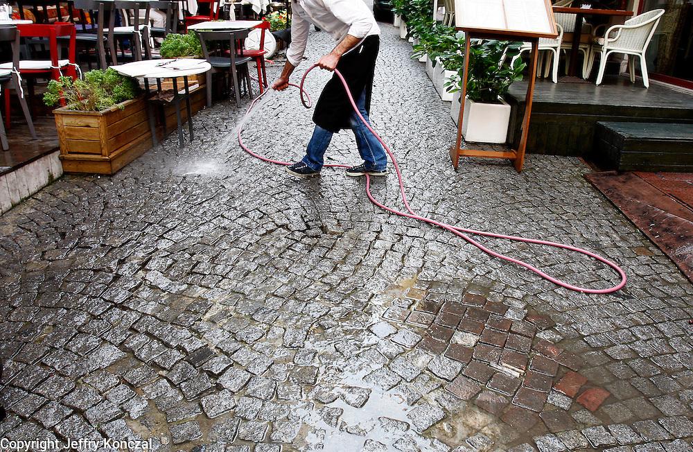 A restuarant employee sprays the street down in Istanbul, Turkey