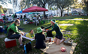 Maeve Snyder, right, places a green hat on her friend Cara Lin, center, in one of the historic squares before the start of the St. Patrick's Day parade, Tuesday, March 17, 2015, in Savannah, Ga. Savannah has been celebrating St. Patrick's Day for 191 years, there have been at least six years without a parade. (AP Photo/Stephen B. Morton)