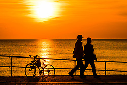 ©Licensed to London News Pictures. 13/095/2019. Aberystwyth UK. A glorious golden sunset over the waters of Cardigan Bay at Aberystwyth bringing to an end a day pf unbroken warm spring sunshine as a high pressure system dominates the weather over the whole of the UK .<br />