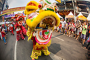 "10 FEBRUARY 2013 - BANGKOK, THAILAND: Chinese Lion dance being performed on Chinese New Year on Yaowarat Road in the Chinatown section of Bangkok. Bangkok has a large Chinese emigrant population, most of whom settled in Thailand in the 18th and 19th centuries. Chinese, or Lunar, New Year is celebrated with fireworks and parades in Chinese communities throughout Thailand. The coming year will be the ""Year of the Snake"" in the Chinese zodiac.    PHOTO BY JACK KURTZ"