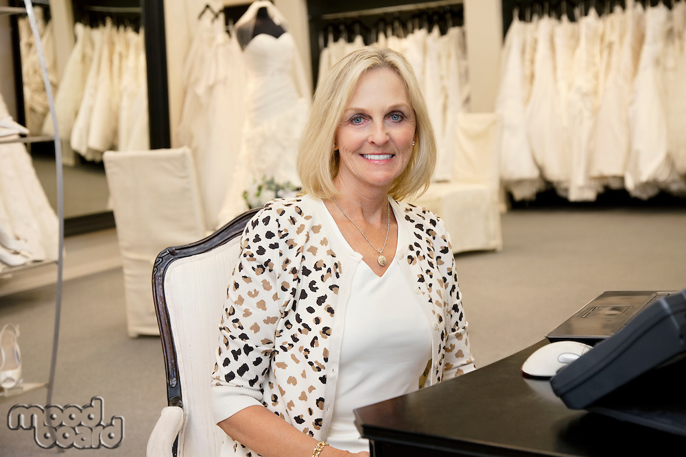 Portrait of a happy senior woman sitting in bridal store