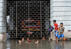 Boys playing in front of a flooded fire station of central Kolkata.