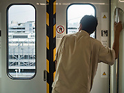 """23 AUGUST 2016 - NONTHABURI, NONTHABURI, THAILAND: A passenger looks out the window on a """"Purple Line"""" train, the new Bangkok commuter rail line that runs from Bang Sue, in Bangkok, to Nonthaburi, a large Bangkok suburb. The Purple Line is run by the  Metropolitan Rapid Transit (MRT) which operates Bangkok's subway system. The Purple Line is the fifth light rail mass transit line in Bangkok and is 23 kilometers long. The Purple Line opened on August 6 and so far ridership is below expectations. Only about 20,000 people a day are using the line; officials had estimated as many 70,000 people per day would use the line. The Purple Line was supposed to connect to the MRT's Blue Line, which goes into central Bangkok, but the line was opened before the connection was completed so commuters have to take a shuttle bus or taxi to the Blue Line station. The Thai government has ordered transit officials to come up with plans to increase ridership. Officials are looking at lowering fares and / or improving the connections between the two light rail lines.     PHOTO BY JACK KURTZ"""