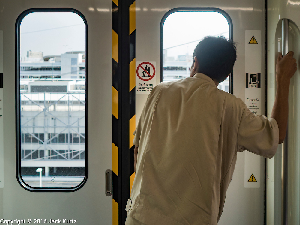 "23 AUGUST 2016 - NONTHABURI, NONTHABURI, THAILAND: A passenger looks out the window on a ""Purple Line"" train, the new Bangkok commuter rail line that runs from Bang Sue, in Bangkok, to Nonthaburi, a large Bangkok suburb. The Purple Line is run by the  Metropolitan Rapid Transit (MRT) which operates Bangkok's subway system. The Purple Line is the fifth light rail mass transit line in Bangkok and is 23 kilometers long. The Purple Line opened on August 6 and so far ridership is below expectations. Only about 20,000 people a day are using the line; officials had estimated as many 70,000 people per day would use the line. The Purple Line was supposed to connect to the MRT's Blue Line, which goes into central Bangkok, but the line was opened before the connection was completed so commuters have to take a shuttle bus or taxi to the Blue Line station. The Thai government has ordered transit officials to come up with plans to increase ridership. Officials are looking at lowering fares and / or improving the connections between the two light rail lines.     PHOTO BY JACK KURTZ"