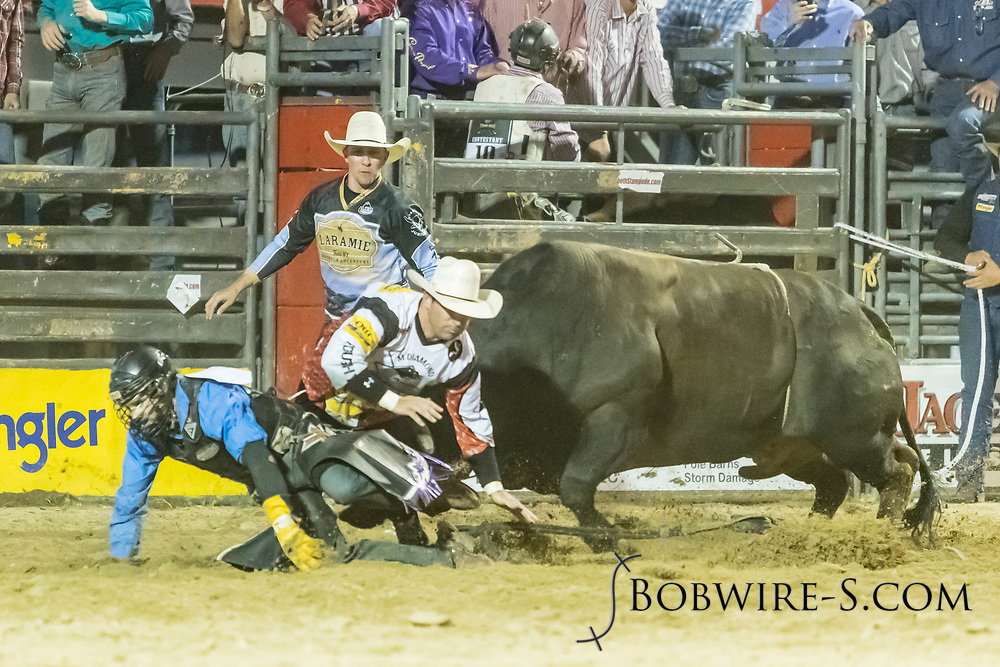 Bullfighters Nate Jestes (in the light shirt) and Cade Burns protect Clayton Savage from Summit Pro Rodeo's 28 Shenanigans SM during the Xtreme Bulls event at the Elizabeth Stampede on Friday, June 1, 2018.