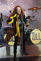 Scottish flautist and leader of rock group Jethro Tull perfoming on stage with a pint of beer in his hand, circa 1975.