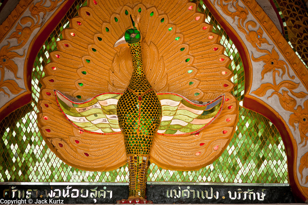 "28 JUNE 2011 - CHIANG MAI, THAILAND:  A peacock over the door to the ""viharn"" or lecture hall, at a Buddhist temple near Chiang Mai, Thailand. Temple in northern Thailand were built in a variety of styles including Laotian, classical Thai, Lanna (also called northern Thai) and Burmese. The peacock over the door means the temple is built in the Burmese style and probably has a history of close ties with Chiang Mai's Burmese population, which in the past included teak traders.  PHOTO BY JACK KURTZ"