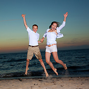 Photo of siblings jumping at sunset at Crosby Beach in Brewster