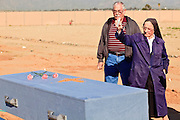"""18 MARCH 2010 - SURPRISE, AZ: Sister Mary Ruth Dittman (CQ) sprinkles holy water on a casket in White Tanks Cemetery on Camelback Rd. in an unincorporated part of the county near Surprise. The county spent about $2.5 million to inter indigent people in what is Maricopa County's """"potters field."""" About 3,000 people, children and adults, are buried in the dusty field west of Phoenix.       PHOTO BY JACK KURTZ"""