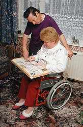 Woman with disability; who is wheelchair user; and husband completing newspaper crossword,