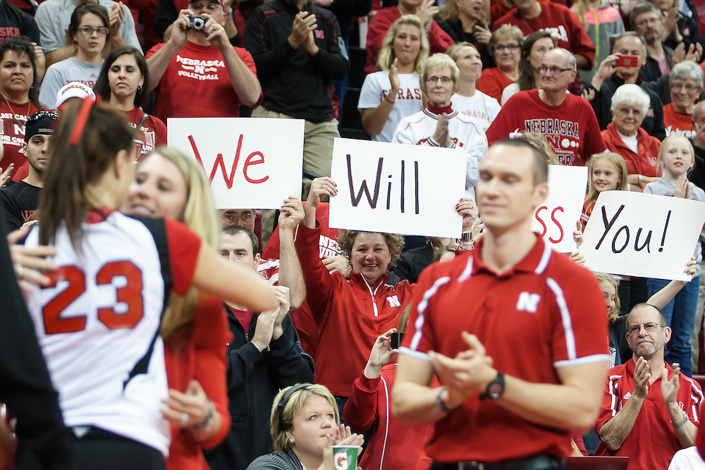 "November 30, 2013: Husker fans hold up sign saying ""We will miss you!"" for the seniors as Kelsey Robinson (23) hugs Dani  Busboom Kelly and Dan Meske at the Devaney Sports Center in Lincoln, Nebraska."
