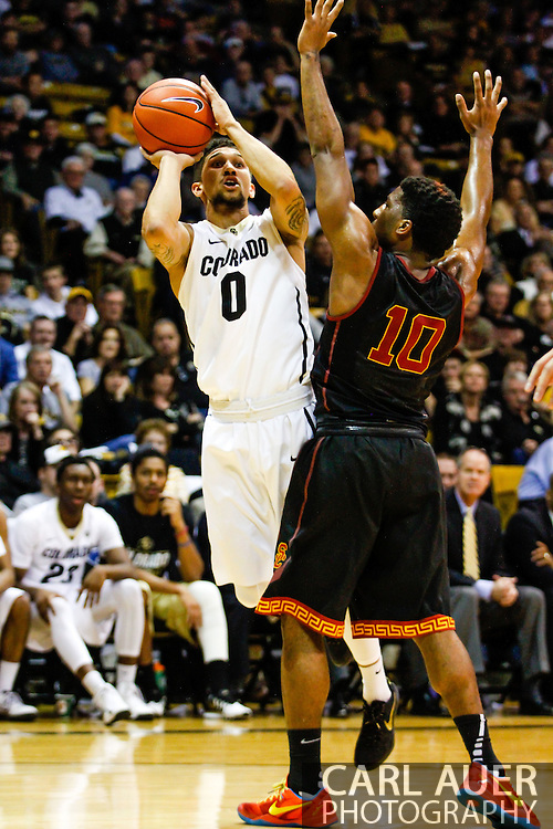 January 18th, 2014:  Colorado Buffaloes junior guard Askia Booker (0) shoots the ball past USC Trojans senior guard Pe'Shon Howard (10) in the second half of action in the NCAA Basketball game between the USC Trojans and the University of Colorado Buffaloes at the Coors Events Center in Boulder, Colorado