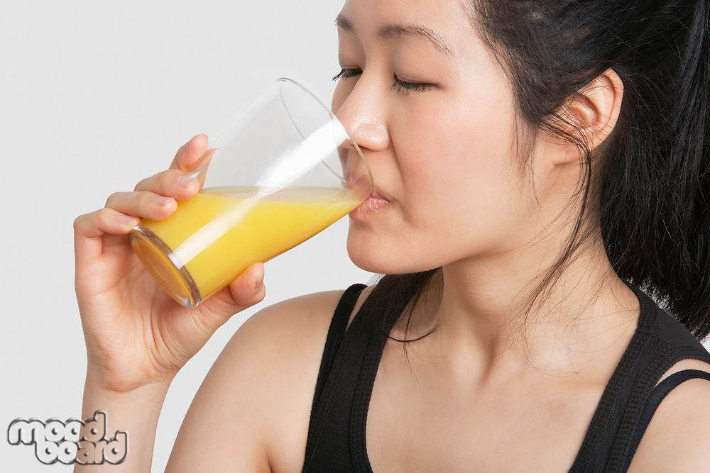 Young woman drinking orange juice over gray background