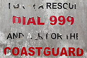 The detail of a peeling beach sign for the 999 emergency Coastguard service, on 31st March 2019, in Whitstable, Kent, England.