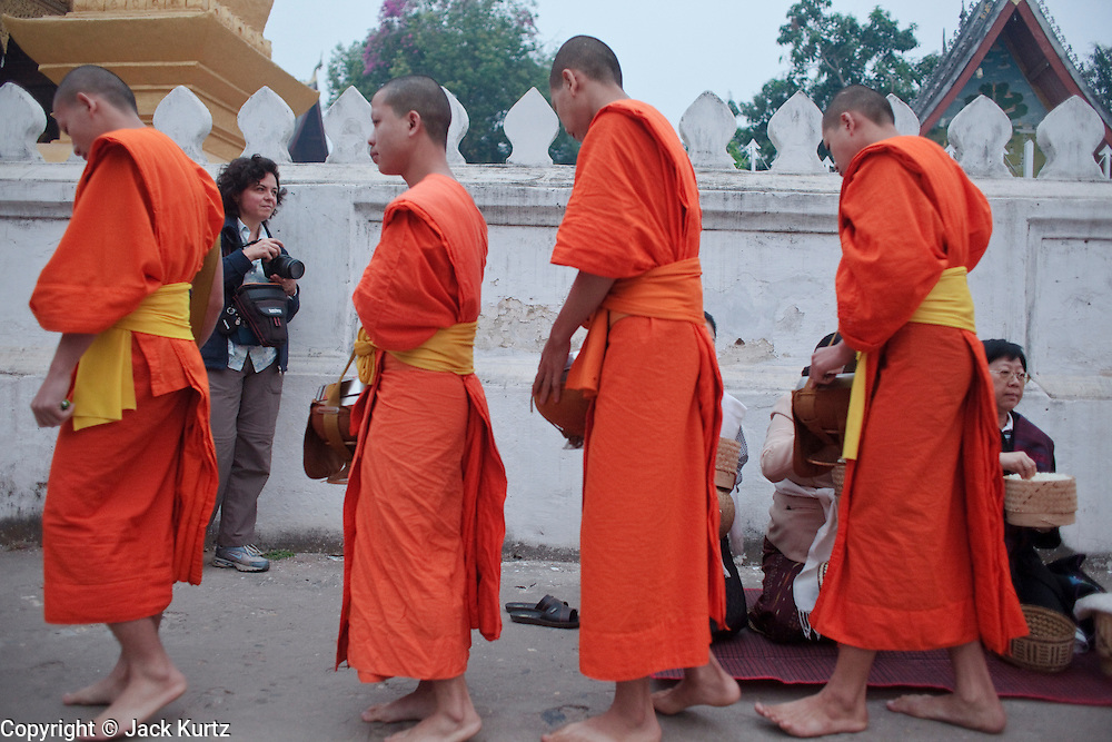 """15 MARCH 2009 -- LUANG PRABANG, LAOS: A tourist in Luang Prabang, Laos, photographs Buddhist Monks as they go about their """"Tak Bat,"""" Lao for """"monks morning rounds."""" The monks collect alms in the form of food from people who line their route. For the monks, it is the only food they get that day, for the people it's a chance to """"make merit."""" Luang Prabang is a UNESCO World Heritage Site and the spiritual capital of Laos. There are dozens of """"wats"""" or temples and thousands of monks in the city. It is still the center of Buddhist education in Laos. Photo By Jack Kurtz"""
