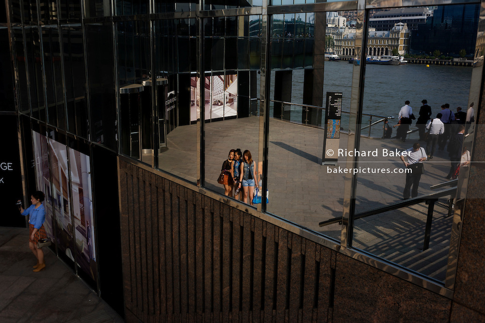 A group of girls pose for a friend's camera, seen reflected in plate glass on the south bank of the River Thames.