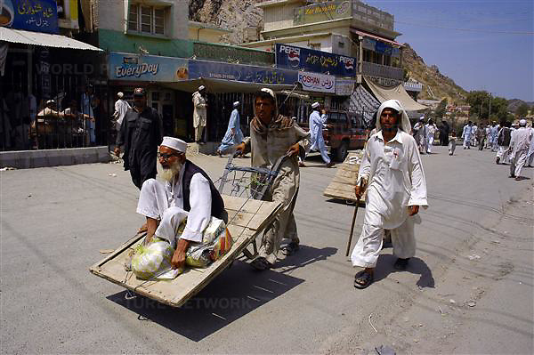 Men walk across the border from Afghanistan into Pakistan at the Torkham border post in Peshawar, Pakistan on Monday Aug. 7, 2006. Torkham is the most important border crossing on the northeast transit route between Afghanistan and Pakistan. The Torkham border processes around 1,400 vehicles per day, 79% of which is heavy truck and cargo traffic. Long lines of vehicles and oil tankers can also be seen across the Torkham border between Afghanistan and Pakistan as Afghan officials stop them for fear of terrorism.