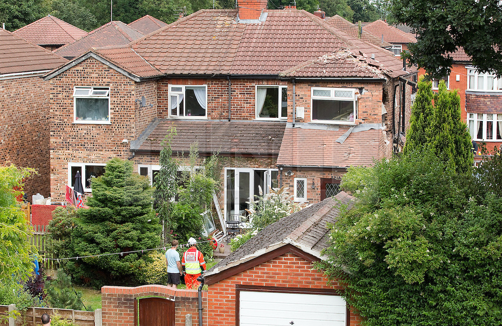 © Licensed to London News Pictures. 29/07/2011. Salford, UK. A fireman surveys the scene with the house's owner. A light aircraft has crashed in to the side of a house near Barton Aerodrome, in Salford, Greater Manchester. No one was killed. Photo credit : Joel Goodman/LNP