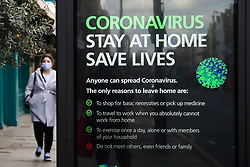 © Licensed to London News Pictures. 31/03/2020. London, UK. A woman wearing a face mask walks next to a 'Coronavirus Stay at Home Save Lives' public information poster in north London as lockdown continues. Photo credit: Dinendra Haria/LNP