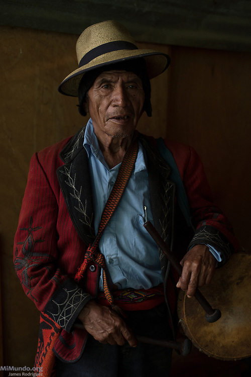 Ixil Mayan elder Nicolas Bernal Ramirez, 79, holding a Cortez drum, poses for a photograph as dozens of residents from Nebaj gather to receive the human remains of 36 war victims. Most of the victims, exhumed from mass graves in Xe'xuxcap, near Acul, starved in the mountainside while fleeing State-led repression in 1982. Most of the remains, exhumed by members of the Forensic Anthropology Foundation of Guatemala (FAFG) in 2013, were identified using DNA analysis and buried 35 years after their death. Acul, Nebaj, Quiché, Guatemala. February 2, 2017.