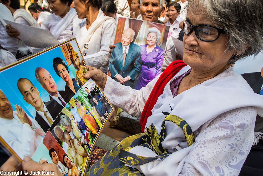 03 FEBRUARY 2013 - PHNOM PENH, CAMBODIA: A woman looks photos of former King Norodom Sihanouk, who ruled Cambodia from independence in 1953 until he was overthrown by a military coup in 1970, while she and others pray for the late King on the sidewalk in front of the National Museum, site of Sihanouk's crematorium. The only music being played publicly is classical Khmer music. Sihanouk died in Beijing, China, in October 2012 and will be cremated during a state funeral royal ceremony on Monday, Feb. 4.     PHOTO BY JACK KURTZ