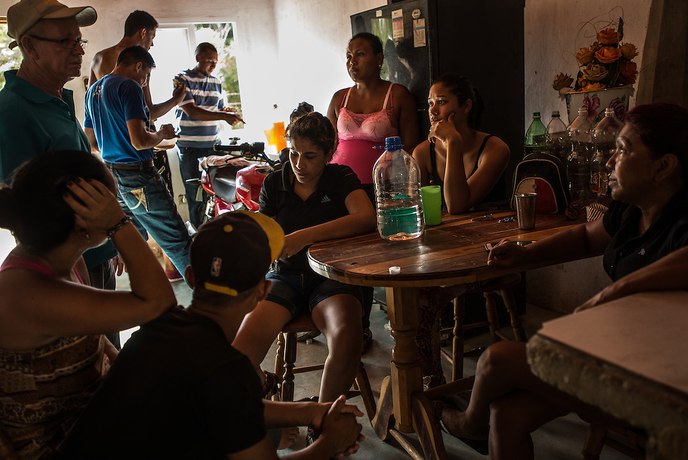 FALCÓN, VENEZUELA - SEPTEMBER 26, 2016: Undocumented migrants wait inside the safe house for the smuggler's boat to arrive that will illegally take them from Venezuela to Curaçao. Undocumented migrants here have mortgaged property, sold kitchen appliances and even borrowed money from the same smuggling rings that pack them on the floorboards alongside drugs and other contraband. The journey to Curaçao takes them on a 60-mile crossing filled with backbreaking swells, gangs of armed boatmen and coast guard vessels looking to capture migrants and send them home. Then, after being tossed overboard and left to swim ashore, they hide in the brush to meet contacts who spirit them anew into the tourist economy of this Caribbean island. They clean the floors of restaurants, work in construction, sell trinkets on the street, or even solicit Dutch tourists for sex. But at least, the migrants say, there is food. PHOTO: Meridith Kohut for The New York Times