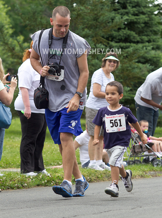 Middletown, New York - A man with a camera walks next to his son during the kids dash at the 16th annual Ruthie Dino-Marshall 5K Run/Walk hosted by the Middletown YMCA on Sunday, June 10, 2012.