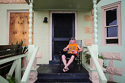 September 10, 2017 - St. Petersburg, Florida, U.S. - ANDY LAWHEAD checks his phone from the front porch of Pass-a-Grille's Sand Castle hotel ahead of Hurricane Irma. ''This could all be gone tomorrow,'' he mused, drinking coffee from a red cup. Lawhead manages the hotel and plans to ride out the storm inside. (Credit Image: © Will Vragovic/Tampa Bay Times via ZUMA Wire)
