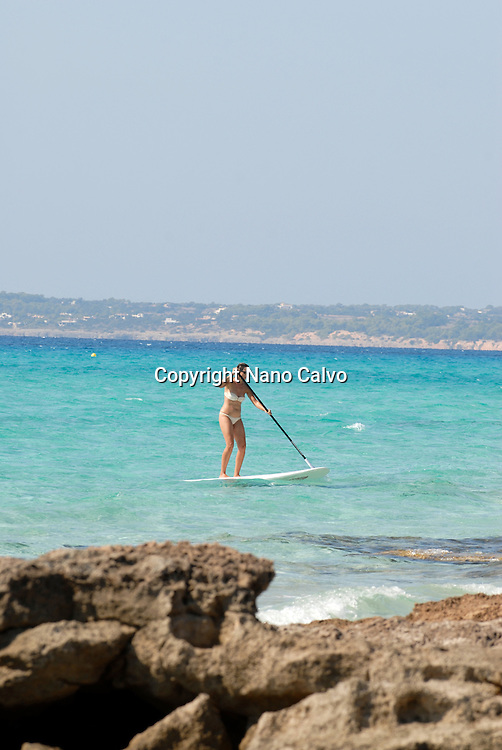 Young woman paddle surfing at Migjorn beach, Formentera