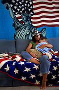 Tracy Acuna cuddles with her son Spencer, 3, on a rainy afternoon, sitting on and in front of blankets sent by her husband Tony from Iraq.  He is with the National Guard and now stationed near Baghdad, his tour now extended until Spring.