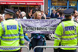 "Cricklewood, London, July 19th 2014. A woman counter-protesting the demonstration by the anti-Islamist ""South East Alliance"", displays her pro-immigration banner."