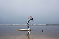 Female surfer standing in shallow water side view