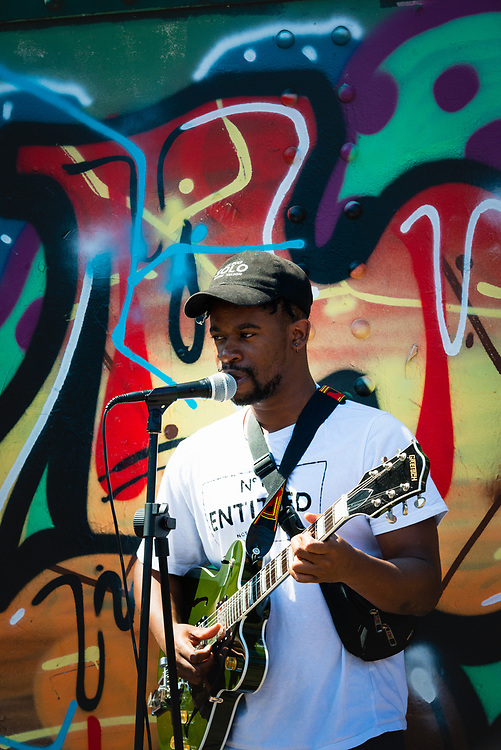 Busker performing in front of colourful street art at Brick Lane market