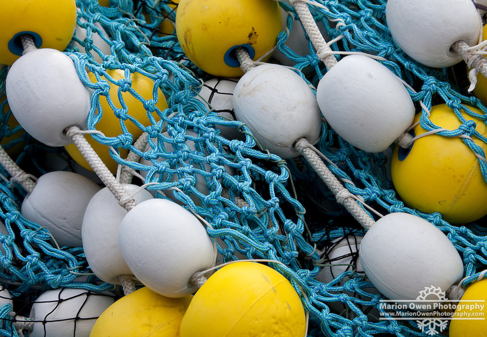 Bright yellow and white corks contrast the sky blue net stacked on deck of a commercial fishing vessel in Kodiak, Alaska.