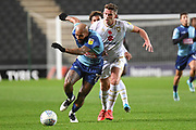 Wycombe Wanderers forward Josh Parker (27) battles for possession  with Milton Keynes Dons midfielder Jordan Houghton (24) during the EFL Trophy match between Milton Keynes Dons and Wycombe Wanderers at stadium:mk, Milton Keynes, England on 12 November 2019.
