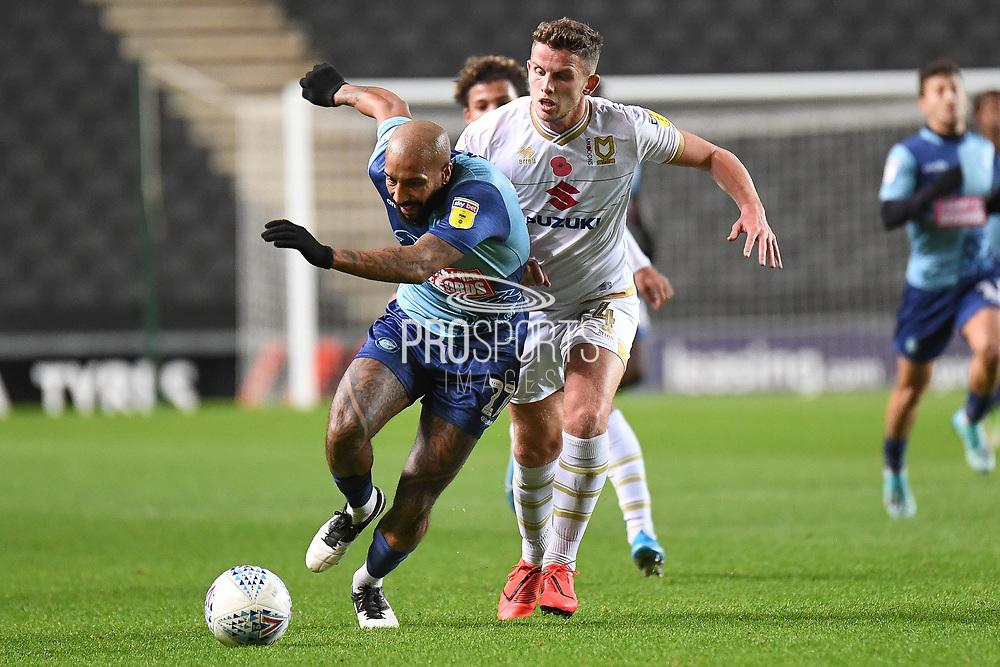 Wycombe Wanderers forward Josh Parker (27) battles for possession  with Milton Keynes Dons midfielder Jordan Houghton (24) during the EFL Trophy match between Milton Keynes Dons and Wycombe Wanderers at stadium:mk, Milton Keynes, England on 12 November 2019.
