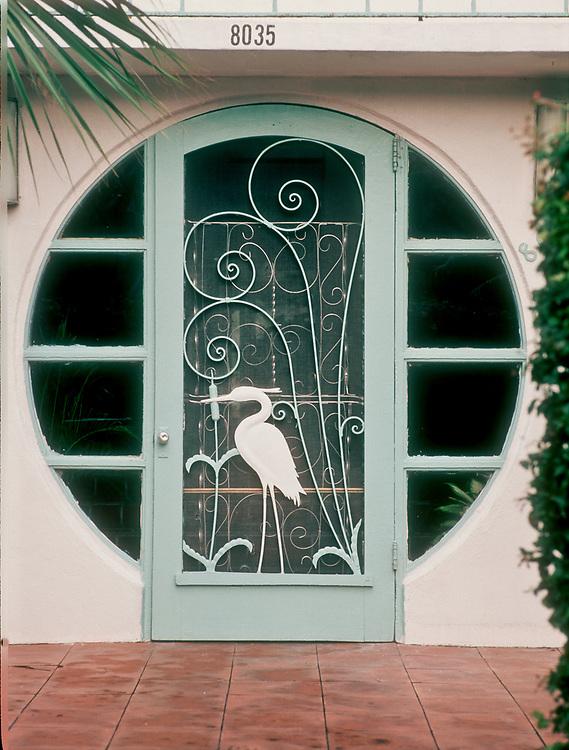 A Tropical Deco door inset in a circular entranceway to a building in Mid-Miami Beach.