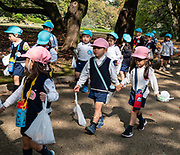 "Young kids in school uniforms parade through Shinjuku Gyoen National Garden, Tokyo, Japan. Shinjuku Gyoen originated during the Edo Period (1603-1867) as a feudal lord's Tokyo residence. Later it was converted into a botanical garden before being transferred to the Imperial Family in 1903 who used used it for recreation and the entertainment of guests. The park was almost completely destroyed during World War II, but was eventually rebuilt and reopened in 1949 as a public park. Access Shinjuku Gyoen park via three gates: Shinjuku Gate is a ten minute walk east from the ""New South Exit"" of JR Shinjuku Station or a five minute walk from Shinjukugyoenmae Station on the Marunouchi Subway Line. Okido Gate is a five minute walk from Shinjukugyoenmae Station on the Marunouchi Subway Line. Sendagaya Gate is a five minute walk from JR Sendagaya Station on the local Chuo/Sobu Line."