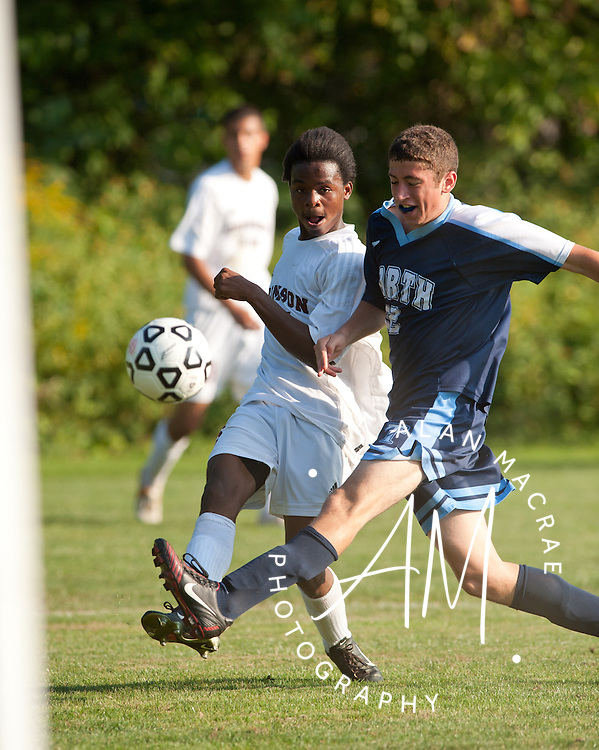 Concord's Rizi Misiri gets a shot off ahead of a block attempt by Nashua North's Devin Motivala during Tuesday's game at Concord's Memorial Field.  (Alan MacRae/for the Monitor)