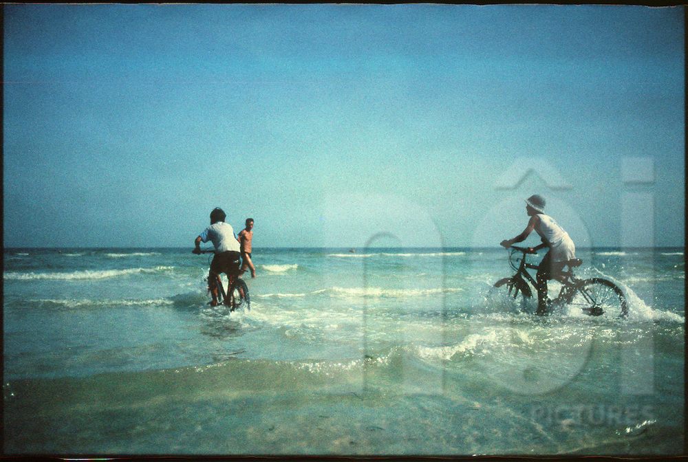 Kids riding bicycles in the water of Sao beach in Phuc Quoc island, Vietnam, Asia
