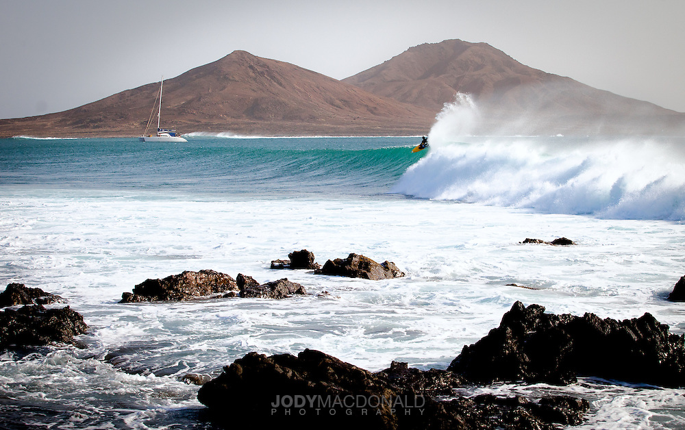 Kiteboarder on big wave in the Cape Verdes with catamaran and mountains in background