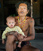 Mentawai indigenous man with baby daughter (Indonesia).