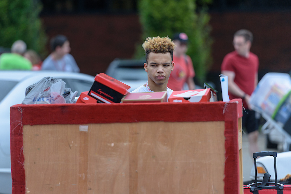 Freshman Anthony Calvin, 18, looks at his stuff in a cart before moving it to Unitas Hall as first-time students move in to Belknap Campus dormitories Wednesday during University of Louisville's Welcome Week. Aug. 17, 2016