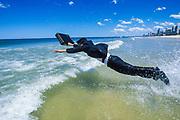 Businessman diving into sea with briefcase, Queensland, Australia