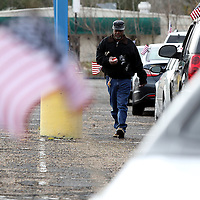 Adam Robison | BUY AT PHOTOS.DJOURNAL.COM<br /> Larry Fisher, of Tupelo, with flags and tape in hand, walks the line of parked cars that are lined up for this years MLK Motorcade that starts at the VF Outlet and travels to St. Paul United Methodist Church for the Dr. Martin Luther King Birthday Celebration Monday morning in Tupelo.