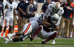 Auburn linebacker Deshaun Davis (57) tries to strip the ball away from Texas A&M wide receiver Christian Kirk (3) as Auburn defensive back Stephen Roberts (14) makes a tackle during the fourth quarter of an NCAA college football game on Saturday, Nov. 4, 2017, in College Station, Texas. (AP Photo/Sam Craft)